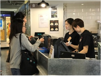 Photo of student volunteer serving as a cashier